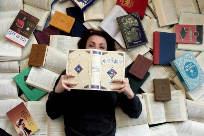 Student laying on a pile of books